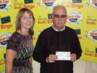 Orla McGuinness presenting a Rehab Radio Bingo Cheque for 600 to MIchael Brennan from Lower Caim, Enniscorthy, who bought her book in Downtown News, South Main Street